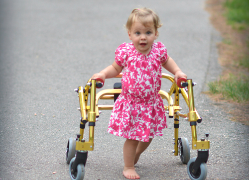 a toddler walking down the sidewalk with a walker